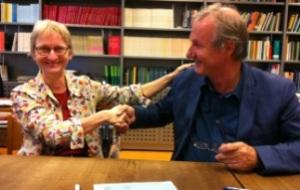 Voorzitter van het NDA Susanne Neugebauer en directeur van het Meertens Instituut Hans Bennis wensen elkaar geluk na de overdracht van de collectie.